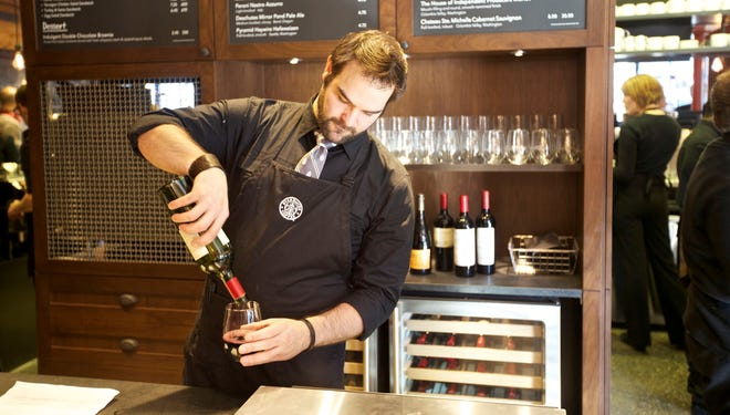 Michael Rotman-Koenen pours a glass of wine at the wine bar in the new Starbucks in Seattle.