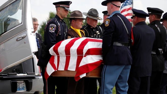 The coffin carrying Officer Jason Ellis' body is brought into the Highview Cemetery in Chaplin, Ky., on Thursday, May 30, 2013.