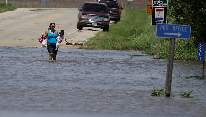 Delfina Ordaz carries her daughter, Fatima Alcaraz, across a flooded road to get to her home on Friday in Chelsea.