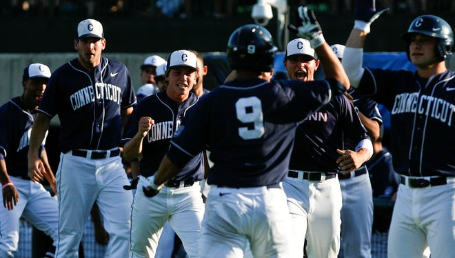 Connecticut third baseman Vinny Siena (9) celebrates with teammates after scoring a run during an NCAA college regional tournament baseball game against Virginia Tech, Friday, May 31, 2013, at English Field in Blacksburg, Va.
