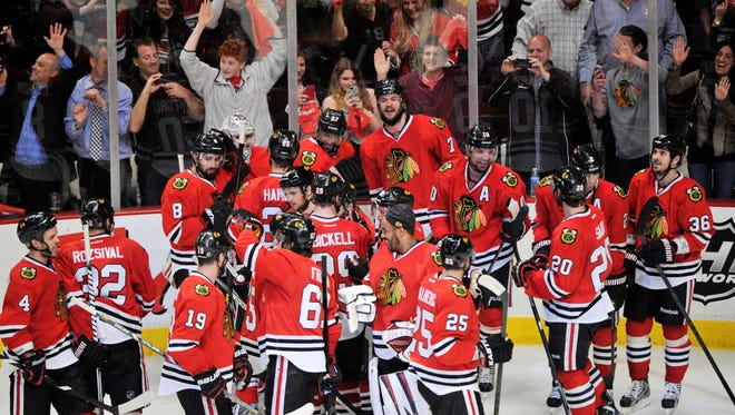 Chicago Blackhawks defenseman Brent Seabrook (7) is mobbed by his teammates after scoring the game-winning goal against the Detroit Red Wings in overtime in Game 7.
