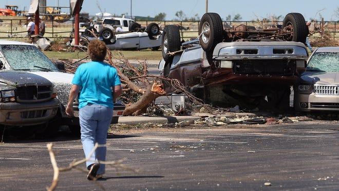 A person looks at cars damaged by a tornado in El Reno, Okla.