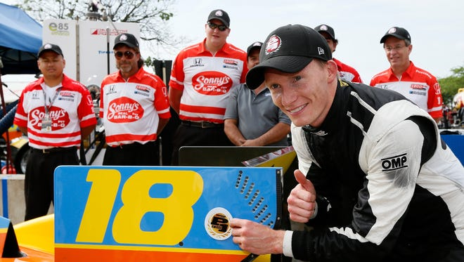 Mike Conway poses with the Verizon Pole Award after qualifying first for the second of two races at the Chevrolet Indy Dual in Detroit.