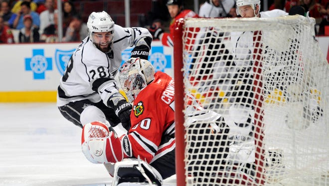 Chicago Blackhawks goalie Corey Crawford makes a save in front of Los Angeles Kings center Jarret Stoll during the second period.