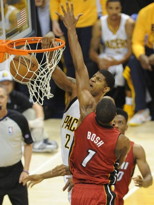 Pacers forward Paul George dunks on Heat center Chris bosh during Game 6 of the Eastern Conference finals.