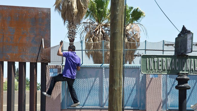 A Mexican man tries to jump the border near a U.S. port of entry on May 30, 2013.