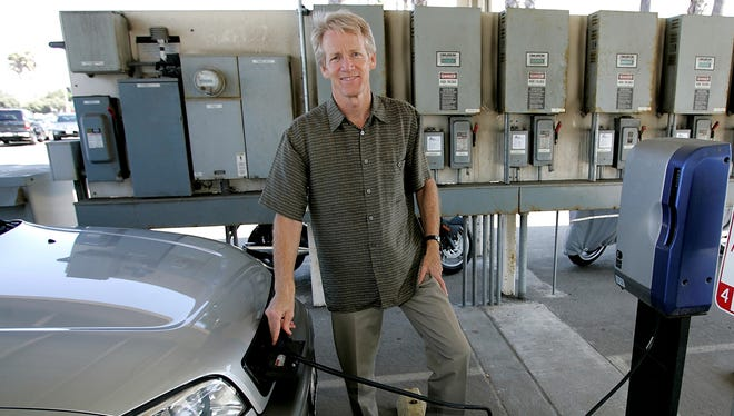 Paul Scott recharges an electric car in this 2005 file photo