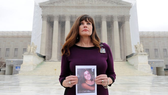 Jayann Sepich stands in front of the Supreme Court holding a photograph of her daughter, Katie, in February