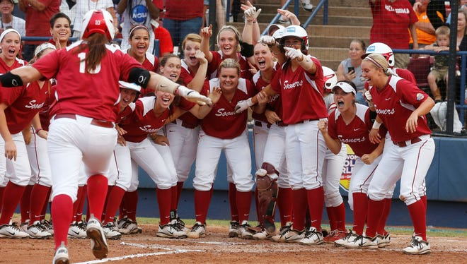 The Oklahoma team waits at home plate for teammate Keilani Ricketts following her home run against Tennessee in the third inning in Oklahoma City.