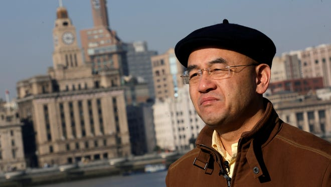 Chinese-born U.S. scientist Hu Zhicheng stands at the waterfront promenade along the Huangpu River in Shanghai, China.