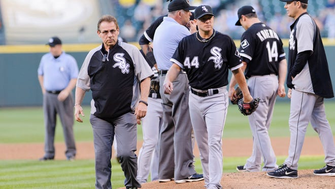 Chicago White Sox trainer Herm Schneider, left, walks off the field with injured starting pitcher Jake Peavy during the third inning against the Seattle Mariners at Safeco Field.