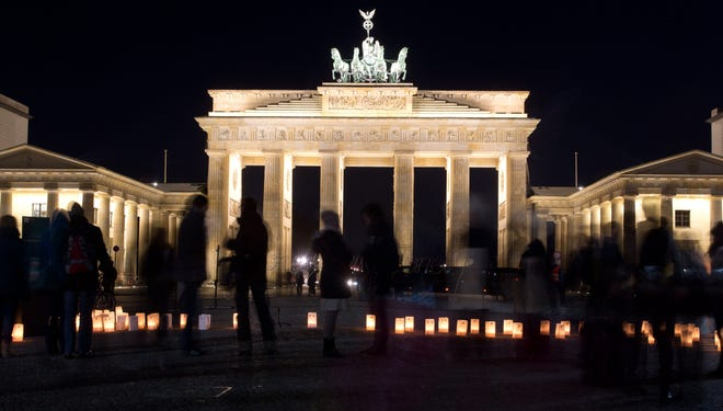"""People arrive at the Brandenburg Gate in Berlin before its lights are gradually turned off as part of the Earth Hour on March 23, 2013.  One minute brightly lit, the next plunged into darkness -- iconic landmarks around the world cut their lights on March 23 for the """"Earth Hour"""" campaign against climate change."""