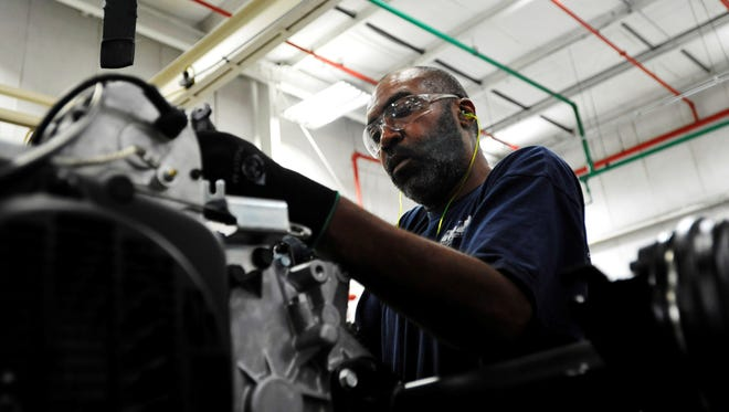 Assembler Richard Lott works on a golf car engine at the E-Z-GO plant in Augusta, Ga.