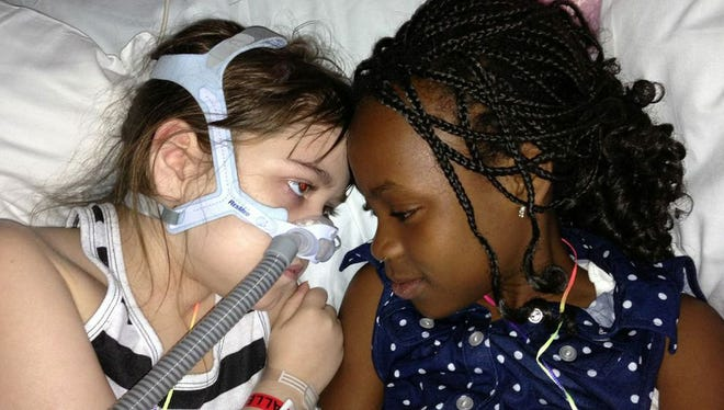 Sarah Murnaghan, left, lies in her hospital bed next to adopted sister Ella. Sarah Murnaghan, left, lies in her hospital bed next to adopted sister Ella