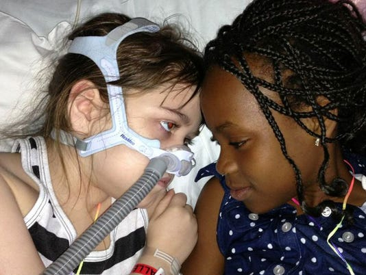 Sarah Murnaghan, left, lies in her hospital bed next to adopted sister Ella