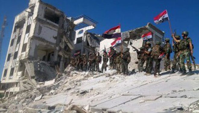 Syrian army troops hold up national flags in the town of Qusair, Homs province, Syria, on June 5, 2013, after retaking the strategic border town near Lebanon.