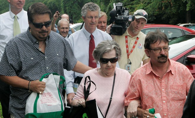 Powerball winner Gloria Mackenzie, 84, leaves the lottery office escorted by her son Scott Mackenzie, right, after claiming her lottery prize.