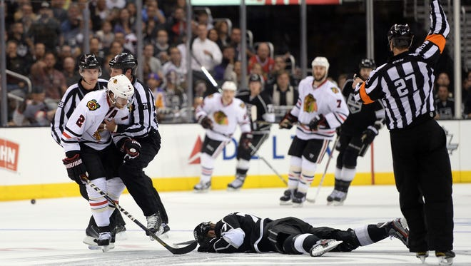 Los Angeles' Jeff Carter lies on the ice after being high-sticked by Chicago's Duncan Keith.
