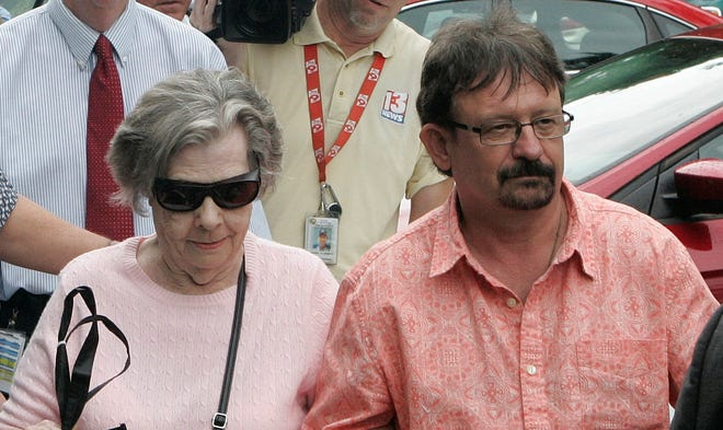 Powerball winner Gloria MacKenzie, 84, left, leaves the lottery office escorted by her son, Scott MacKenzie, after claiming a single, lump-sum payment of about $370 million before taxes in June.