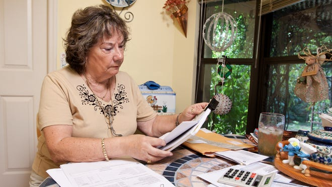 Nelly Rush, 75, looks over reverse mortgage papers from Bank of America. She and her husband took out a reverse mortgage in 2006. After signing the paperwork they found out they owed $11,000 in closing cost fees.