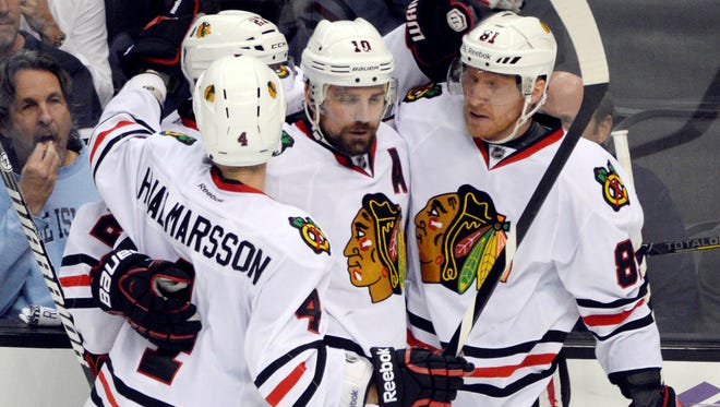 Chicago Blackhawks winger Marian Hossa, right, is congratulated by teammates after breaking a third-period tie.