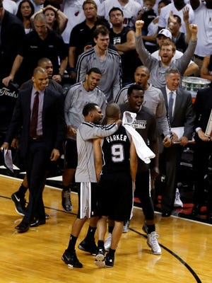 Spurs point guard Tony Parker is surrounded by teammates after making the key shot in Game 1 of the NBA Finals on Thursday.