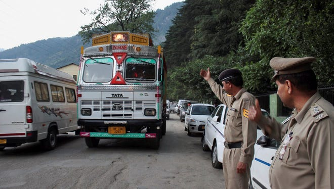 Indian policemen keep a check on vehicles after an American woman was gang-raped in the northern Indian resort town of Manali, India, on June 4, 2013.