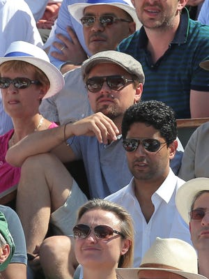 Leonardo DiCaprio and PSG soccer club president Nasser al-Khelaifi, of Qatar (wearing white shirt and dark sunglasses) watch tennis at the French Open on Friday in Paris.