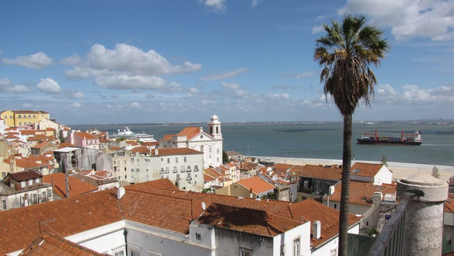The red-tiled rooftops of Lisbon, Portugal's capital, spill to the banks of the Tagus River where it flows into the Atlantic Ocean. Portugese receive a great deal of vacation time.
