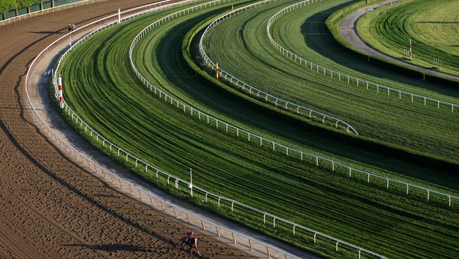 A horse gallops around the fourth turn during a morning workout. Butler is charged with administering steroids to nine horses.