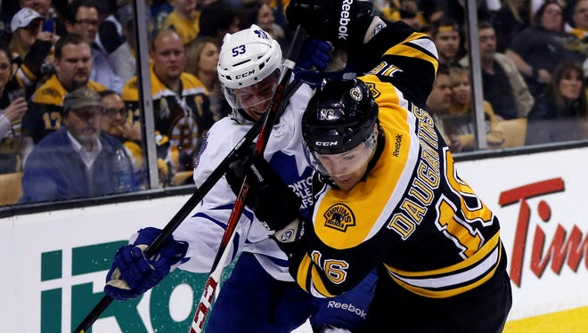 Boston Bruins forward Kaspars Daugavins battles with Toronto Maple Leafs defenseman Mike Kostka during the first round.