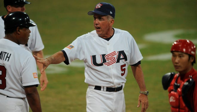 In a file photo from Aug. 8, 2008, U.S. manager Davey Johnson holds back coach Reggie Smith after a player was hit by a pitch during the Beijing Olympics.