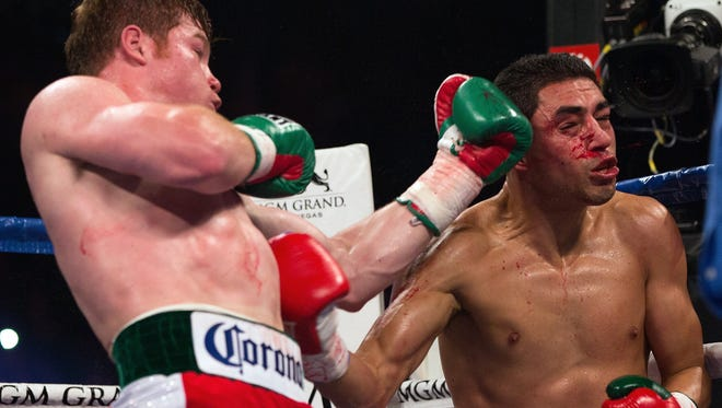 Canelo Alvarez lands a left to the head of Josesito Lopez during their WBC super  welterweight title fight last September. Alvarez won by 5th-round TKO.