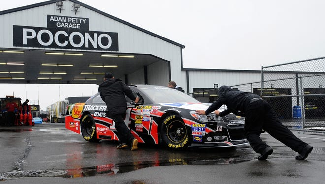 Crew members push Tony Stewart's No. 14 Chevrolet in the garage area during a rain delay at Pocono Raceway Friday.
