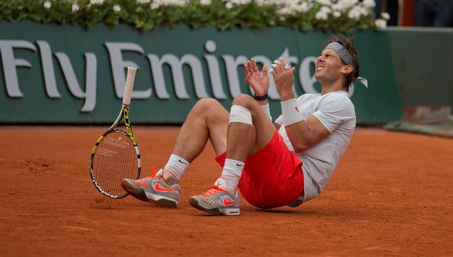 Rafael Nadal of Spain sinks to the clay after defeating compatriot David Ferrer in the French Open final.
