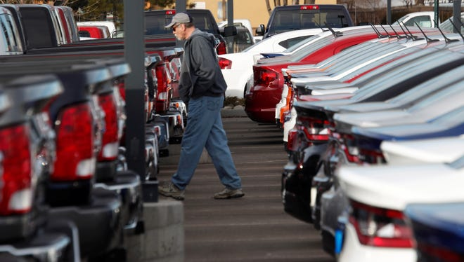 IHS announced Monday that it is buying R.L. Polk, the owner of Carfax. Pictured is a buyer moving between rows at a Dodge dealership in Littleton, Colo.