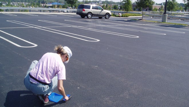 Barbara Mahler, a hydrologist with the U.S. Geological Survey who's researched the hazards of coal tar pavement sealant, takes a sample of parking lot dust in 2007 in Lake In the Hills, a suburb of Chicago.