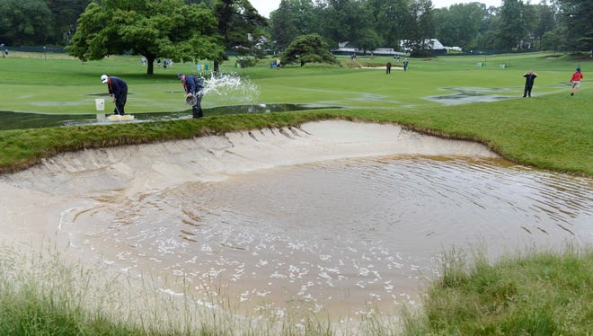 Grounds crews work near the flooded bunker on the 16th hole during a practice round Monday at soggy Merion Golf Club.