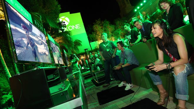 Lisa Malambri experiences her first hands-on time with Ryse: Son of Rome at Xbox Showcase at E3 2013. A new report finds that women make up 45% of today's gamers. (Photo by Casey Rodgers/Invision for Microsoft/AP Images)