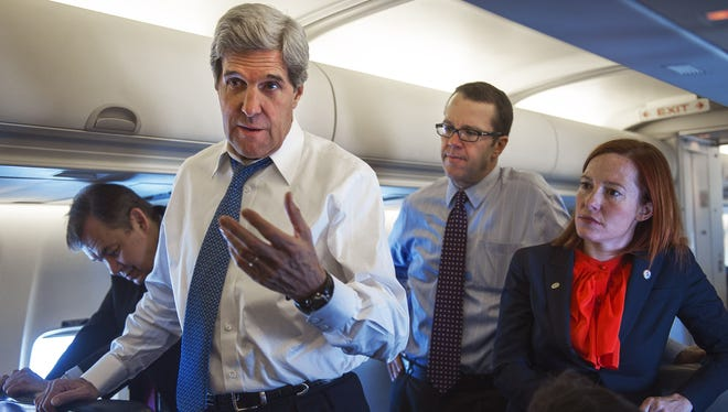 Secretary of State John Kerry, talks with reporters aboard his government aircraft shortly after departing Seoul, South Korea, April 13, 2013. Behind Kerry are senior staff members Glen Johnson and Jen Psaki.