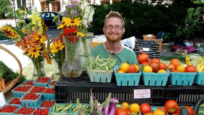 A Michigan State University student staffs the student organic farm stand.
