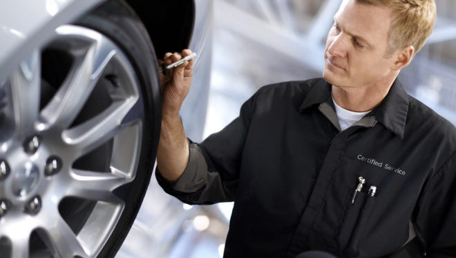 A unnamed General Motors mechanic checks a tire.
