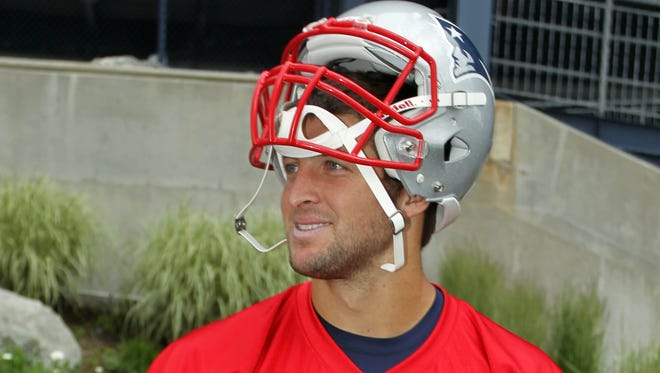 New England Patriots quarterback Tim Tebow signs an autograph for a fan during minicamp at the practice fields of Gillette Stadium on Wednesday.