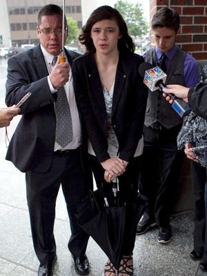 Transgender student Nicole Maines, center, with her father Wayne Maines, left, and brother Jonas Maines, speaks to reporters outside the Penobscot Judicial Center, Wednesday, June 12, 2013, in Bangor, Maine.