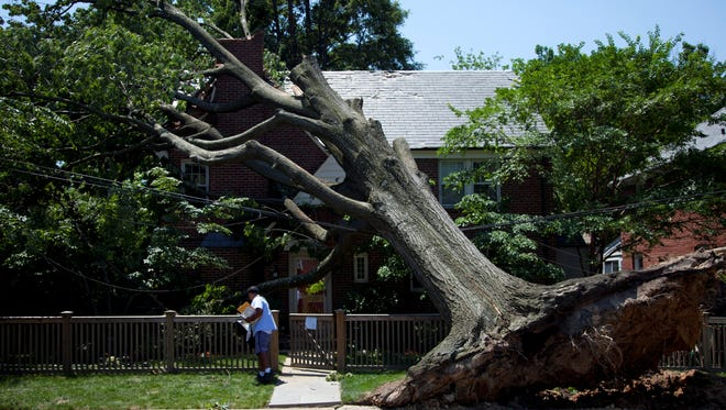A letter carrier for the U.S. Postal Service delivers mail to a residence in Washington that was damaged by a powerful derecho last June.