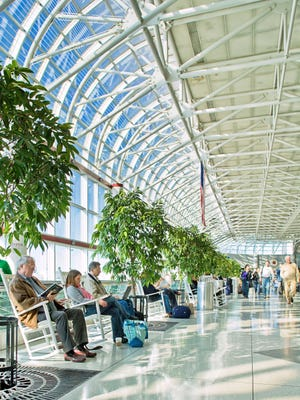 The  atrium at Charlotte Douglas International Airport in North Carolina is lined with trees and white wooden rocking chairs, just like what you might find on a Southern front porch.