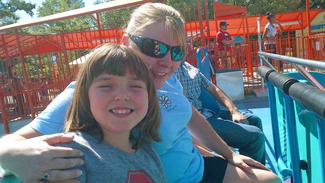 Sherry Yuskewich, right, and daughter Kendall enjoy a ride in 2012 at Kings Island amusement park in Mason, Ohio.  The family makes several trips each year to the park, where they say Kendall, who has autism, always had been permitted to ride rides with little wait time.
