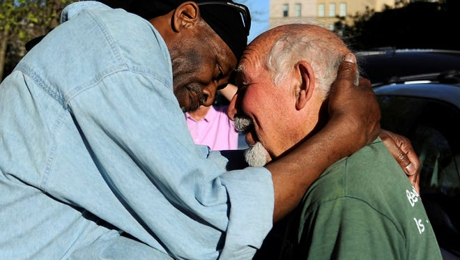 Michael Johnson, left, hugs friend Anthony Cymerys, known as Joe the Barber, in Bushnell Park in Hartford, Conn. on May 1, 2013.