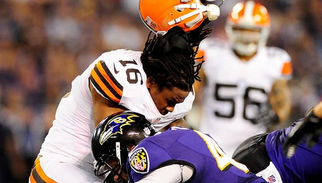 Browns wide receiver Josh Cribbs gets his helmet knocked off by Ravens long snapper Morgan Cox at M,T Bank Stadium in 2012.