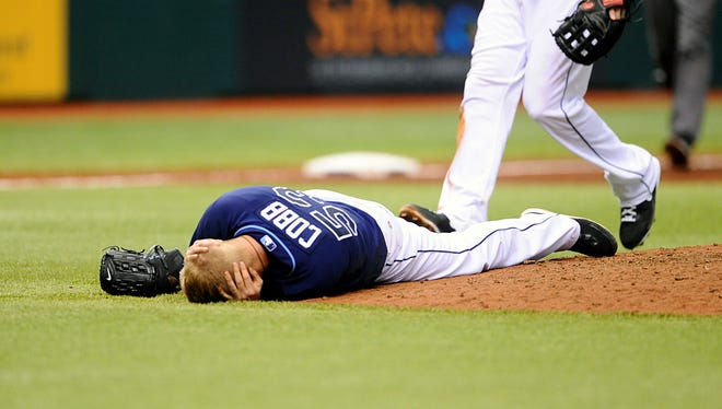 Tampa Bay Rays starting pitcher Alex Cobb grabs his head and lies on the pitcher's mound after being hit by a line drive by Kansas City Royals' Eric Hosmer during the fifth inning in St. Petersburg, Fla.